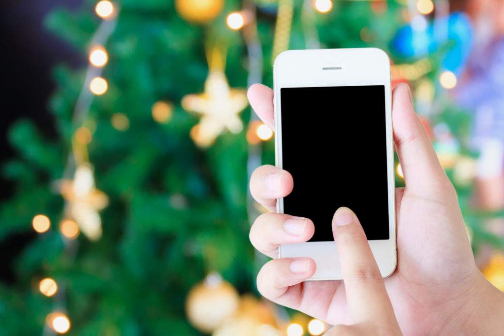 Christmas party concept - hand holding mobile smart phone with Christmas lights bokeh on Xmas tree